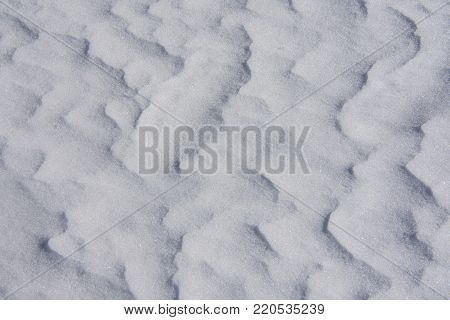 A subtle white crystalline snow drift with a soothing wave pattern. The homogeneous ripple would be perfect for a background where the writing needs to be seen.
