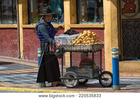 Otavalo, Ecuador-December 23, 2017: indigenous woman selling fruits on the street in the popular tourist town