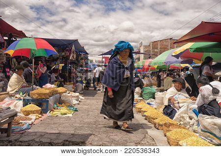 Otavalo,Ecuador-November 25, 2017: an indigenous woman wearing traditional clothing walks through the Saturday farmers market