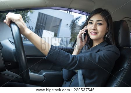 Asian Woman Looking Smartphone While Driving Car To Go To Work, Woman Working Concept.
