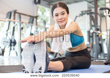 Portrait Of Attractive Young Asian Woman Worm Up Before Exercise At Fitness Club.