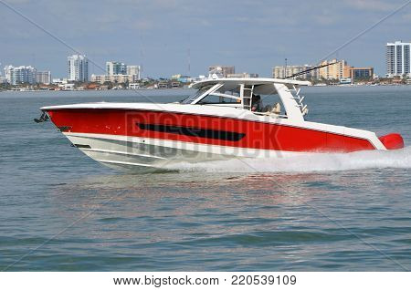 Red and white fishing boat powered by a single outboard engine speeding on the florida intra-coastal waterway off Miami Beach.