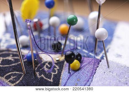 Macro of pins and needles. A conceptual image of pins and needles sticking in a pin cushion.