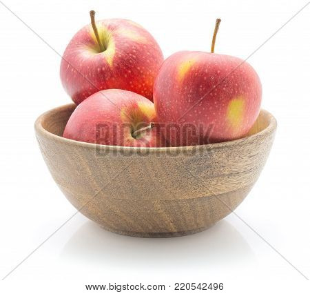 Three apples (Evelina variety) in a wooden bowl isolated on white background red yellow