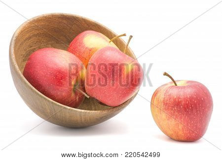 Four apples (Evelina variety) in a wooden bowl isolated on white background red yellow