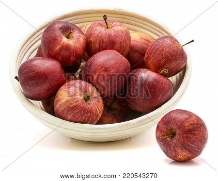 Gala apples in rattan bowl isolated on white background one apple is near