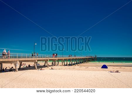 Glenelg, South Australia - February 28, 2016: People  relaxing at Glenelg beach on a bright summer day viewed from Moseley Square