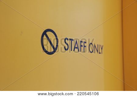 closeup focus on Staff only sign on the yellow entrance door for the security reason. concept of authorization.