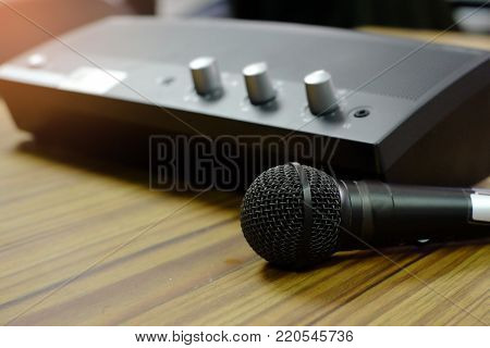 Microphone With Mini Power Amplifier On Wooden Table.