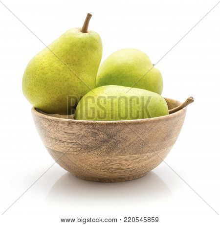 Green pears in a wooden bowl isolated on white background three whole