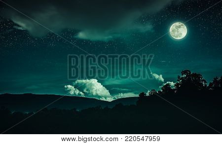Landscape of emeral night sky with many stars and cloudy above silhouette of mountain range and trees. Beautiful bright full moon over tranquil nature on dark tone. The moon taken with my own camera.