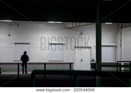 The guy in the hood stands at night under the lanterns near the white wall and is waiting for someone.
