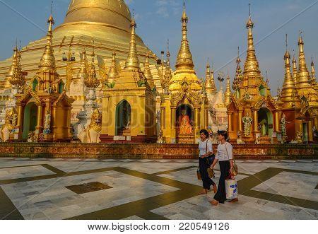 Yangon, Myanmar - Feb 26, 2016. Burmese women walking at Shwedagon Pagoda in Yangon, Myanmar. The Pagoda is believed by Buddhists to be around 2500 years old.