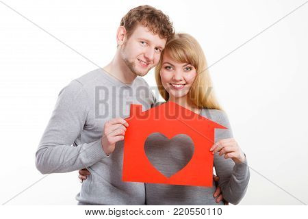 People, fresh start, real estate and love concept. Young enjoyable enamoured marriage holding red house with big heart.
