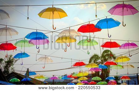 multicoloured umbrellas and cloudy blue sky