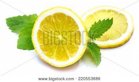 Sliced lemon on fresh green lemon balm leaves isolated on white background