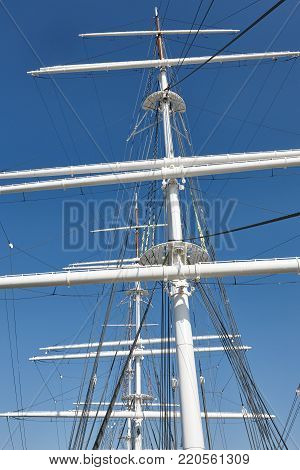 White yatch masts over a blue sky. Nautical background. Vertical