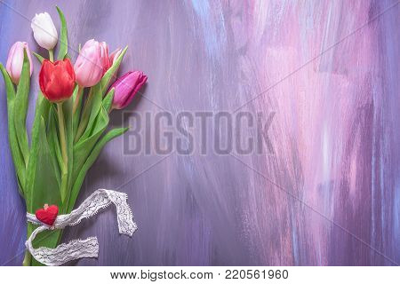 Bouquet of tulips on purple background - Lovely bouquet of colorful tulips tied with lace ribbon and a wooden clip with red heart displayed on a wooden background with many shades of purple.
