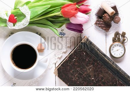 Flowers and old book with coffee and sweets - Romantic breakfast table with a cup of coffee, sweets, an old book, a vintage pocket clock and a bouquet of tulips tied with lace, on a white table.