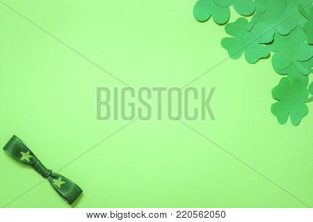 Shamrocks and a green bow tie - Saint Patrick frame design, with a bunch of paper clovers in a corner and a bow tie in the other, displayed on a blank green paper background.