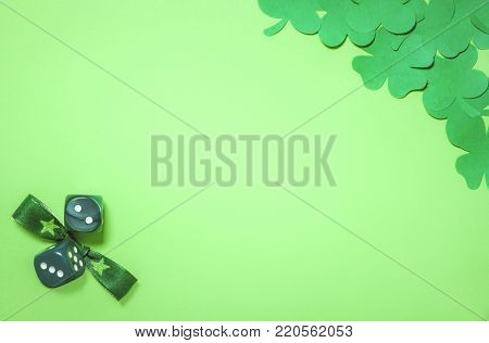 Shamrocks with a bow tie and dice - Saint Patrick concept with dark green paper clovers in a corner and a bow tie and dices in the other, placed on a blank light green paper sheet.