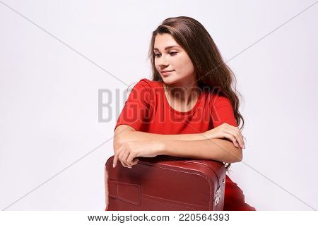 Journey. Girl with a suitcase. Pensive brunette.