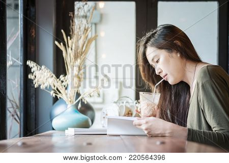 Closeup asian woman reading a book and drinking iced chocolate at the wooden counter desk in coffee shop with happy face on blurred coffee shop view background under window light