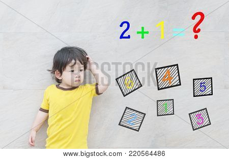 Closeup asian kid with confuse face by mathematic question on marble stone wall textured background