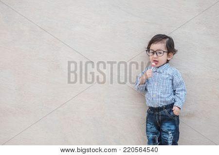 Closeup happy asian kid with eyeglasses eating candy on marble stone wall textured background with copy space