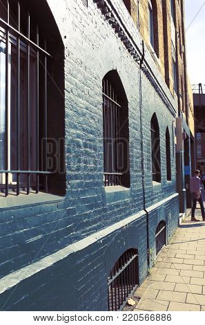 Old retro buiding with iron lattice on the window and painted brick walls.