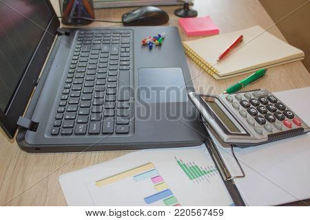 The calculators, accounting and technology, business, computer, laptop, calculator and documents in the office. Office workplace with laptop and calculator on wood table