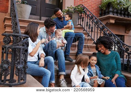Two families with kids sitting on front stoops