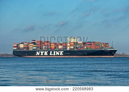 Hollern, Germany - December 29, 2017: Ultra Large Container Ship NYK FALCON on Elbe river heading to Hamburg. It holds up to 14026 TEU and is owned by Japanese shipping company Nippon Yusen Kaisha.