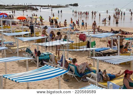 ALBUFEIRA, PORTUGAL - AUGUST 25, 2017: People at the famous beach of Olhos de Agua in Albufeira. This beach is a part of famous tourist region of Algarve.