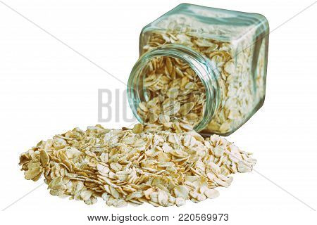 Pour oat flakes or oatmeal from glass bottle on white isolated background with clipping paths. Rolled oat is clean food for health. Natural organic healthy food concept. Oatmeal on white isolated with clipping paths. Oat flakes for breakfast.