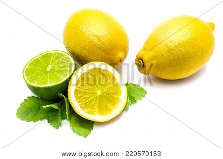 Two whole lemons, lime and lemon half with fresh lemon balm leaves isolated on white background