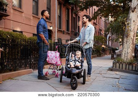 Two father friends with two kids talking in the street