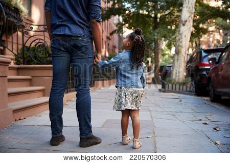 Father and daughter taking a walk down the street, back view