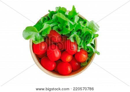 Fresh cherry tomato and lettuce or green oak in wood bowl. Cherry tomato and lettuce on white isolated background with clipping paths in top view flat lay. Prepare fresh tomato and lettuce vegetables for salad cooking. Homemade food concept.