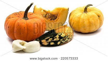 Two whole orange and yellow pumpkin, yellow and white slices with seeds isolated on white background