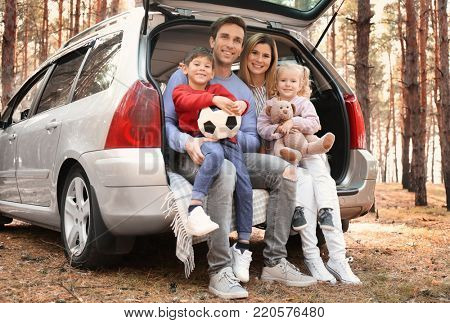 Young couple with their little children sitting in car trunk