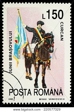 Moscow, Russia - January 03, 2018: A stamp printed in Romania, shows celebrating man with flag riding on a horse, Curcan, series