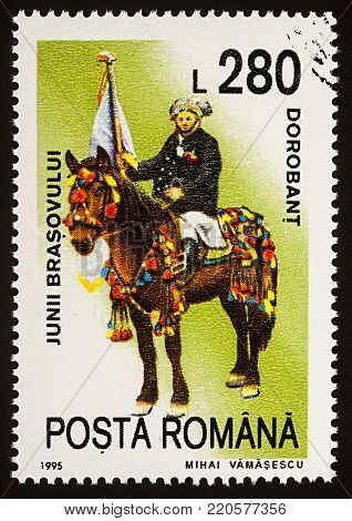 Moscow, Russia - January 04, 2018: A stamp printed in Romania, shows celebrating man with flag riding on a horse, Dorobant, series