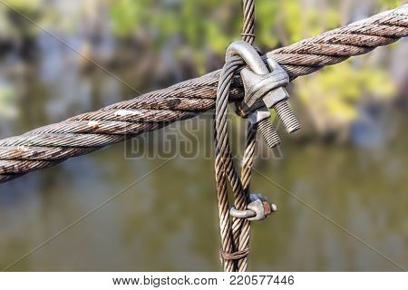 wire rope clamps and rusty steel ropes.  Equipped to hold or pull something and make it connected.