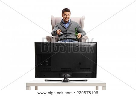 Young guy with a remote control and a bottle of beer sitting in an armchair and watching television isolated on white background