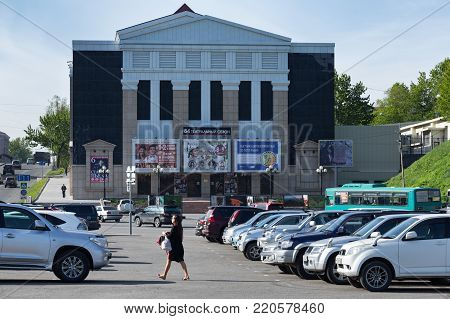 KAMCHATKA PENINSULA, RUSSIAN FAR EAST - JUNE 16, 2017: Summer view on modern facade building of Kamchatka Drama and Comedy Theater and parked cars in square in Petropavlovsk-Kamchatsky City.