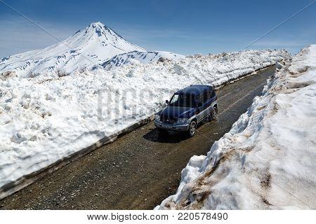 VILYUCHINSKY VOLCANO, KAMCHATKA PENINSULA, RUSSIA - JUNE 18, 2017: Japanese off-road car Mitsubishi Pajero iO driving on mountain road in snow tunnel on background of volcano.