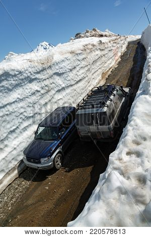 KAMCHATKA PENINSULA, RUSSIA - JUNE 18, 2017: Japanese off-road cars Toyota Land Cruiser Prado and Mitsubishi Pajero iO driving on mountain road in snow tunnel surrounded by high snowdrifts on Vilyuchinsky Pass.