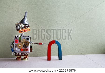 Funny robot red blue horseshoe magnet. Creative design toy funnel hopper, cogs wheels gears silver metallic body. Cyborg checks magnetic field gravity attraction. Green gray background, copy space.