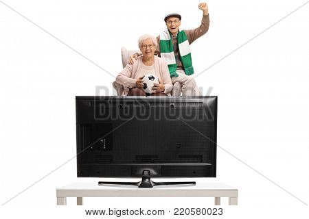 Excited elderly soccer fans with a football and a scarf sitting in an armchair and watching television isolated on white background